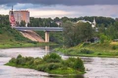 De zomermening van de majestueuze kalme waterstroom en de schilderachtige eiland en steile kust van de Volga rivier met brug in b stock afbeelding