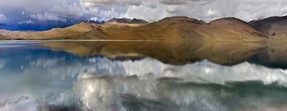 De zomeronweersbui op het hooggebergte van Meer Tso Moriri: sombere grijze en zwarte wolken en spiegeloppervlakte van water, Tibe Stock Foto