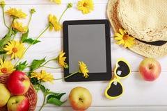 De zomerpatroon met gele bloemen, rode appelen, strohoed, tabl Stock Foto