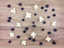 De zomerpatroon van jasmijnbloemen en bessen op houten lijst Vlak leg Stock Foto