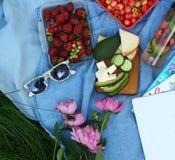 De zomerpicknick in aard op groen gras, grote kom met aardbeien, zonnebril, avocado, pioenen stock afbeelding