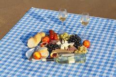 De zomerpicknick op het strand bij zonsondergang Rust met Wijn bij het overzees stock afbeelding