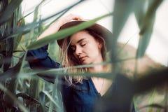 De zomerportret die van jonge hipstervrouw in een gras op zonnige dag liggen Royalty-vrije Stock Foto
