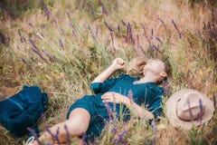 De zomerportret die van jonge hipstervrouw in een gras op zonnige dag liggen Stock Foto