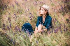 De zomerportret van de jonge zitting van de hipstervrouw in een gras op zonnige dag Stock Afbeeldingen