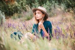De zomerportret van de jonge zitting van de hipstervrouw in een gras op zonnige dag Stock Foto
