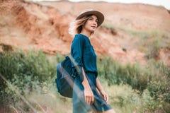 De zomerportret van jonge hipstervrouw status in een gras op zonnige dag Royalty-vrije Stock Afbeelding