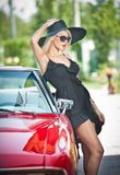 De zomerportret van modieus blonde uitstekende vrouw met lange benen die dichtbij rode retro auto stellen modieus aantrekkelijk e stock fotografie