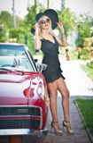 De zomerportret van modieus blonde uitstekende vrouw met lange benen die dichtbij rode retro auto stellen modieus aantrekkelijk e Stock Afbeeldingen