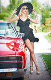 De zomerportret van modieus blonde uitstekende vrouw met lange benen die dichtbij rode retro auto stellen modieus aantrekkelijk e Royalty-vrije Stock Afbeelding