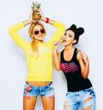 De zomerportret van twee vrij blonde en donkerbruine meisjesvrienden die pret met ananas, spaanders hebben Het zingen met zonnebr Royalty-vrije Stock Foto