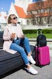 De zomerreis en vakantieconcept - jonge vrouwenzitting met koffer in oude stad stock foto