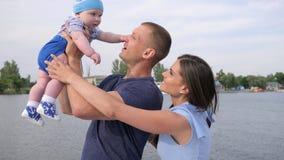 De zomerrest van gelukkig paar met baby op meer, weinig jong geitje in vader` s sterke handen dichtbij van moeder, stock video