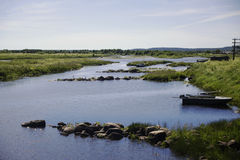 De zomerrivier met steenvensterbanken en een boot Stock Foto