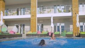 De de zomerrust in poolside, bedrijf van vrolijke lachende meisjes in zwempakken springt in blauw water van pool terwijl het onts stock videobeelden