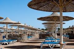 De zomerstrand met paraplu's en lanterfanters Gevlechte paraplu's onder de blauwe hemel Leeg strand Royalty-vrije Stock Fotografie