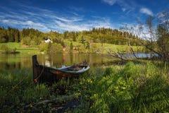 De zomertijd door het Jonsvatnet-meer, middennoorwegen  Houten peddelboot door de kust stock foto