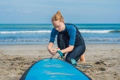 De zomertijd en actief rust concept De jonge beginner van de surfervrouw maakt leiband over been vast, die op grote barral gaan s stock fotografie