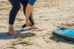 De zomertijd en actief rust concept De jonge beginner van de surfervrouw maakt leiband over been vast, die op grote barral gaan s royalty-vrije stock foto