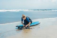De zomertijd en actief rust concept De jonge beginner van de surfervrouw maakt leiband over been vast, die op grote barral gaan s royalty-vrije stock fotografie