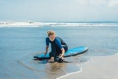 De zomertijd en actief rust concept De jonge beginner van de surfervrouw maakt leiband over been vast, die op grote barral gaan s stock foto