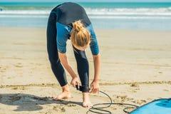 De zomertijd en actief rust concept De jonge beginner van de surfervrouw maakt leiband over been vast, die op grote barral gaan s stock foto's