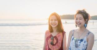 De zomertijd, portret van twee jonge vrouwen die op het strand lopen en het glimlachen stock afbeeldingen