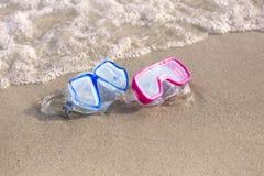 De zomertijd: Rode en blauwe gogles op het zand door de oceaan Stock Foto's