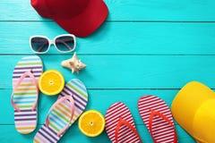 De zomertoebehoren en oranje vruchten op blauwe houten achtergrond Hoogste mening en exemplaarruimte Stock Foto's