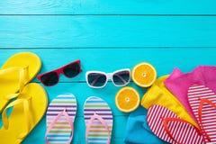 De zomertoebehoren Wipschakelaars, zonnebril, handdoeken en sinaasappelen op blauwe houten achtergrond Hoogste mening en exemplaa Stock Foto's