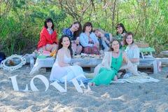 De zomervakantie en vakantie - jonge vrouwen die en op het strand eten drinken stock foto