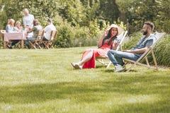 De zomervakantie in groene omgeving Mensen die op dek CH zitten stock afbeelding