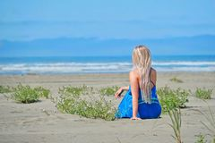 De zomervakantie op strand Vrouw die op strand het overzees bekijken stock foto