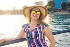 De zomervakantie, vakantie, reis en mensenconcept - glimlachende jonge vrouw die zonnebril en hoed op strand over overzees dragen Royalty-vrije Stock Afbeelding