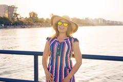 De zomervakantie, vakantie, reis en mensenconcept - glimlachende jonge vrouw die zonnebril en hoed op strand over overzees dragen Royalty-vrije Stock Fotografie