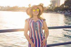 De zomervakantie, vakantie, reis en mensenconcept - glimlachende jonge vrouw die zonnebril en hoed op strand over overzees dragen Stock Foto