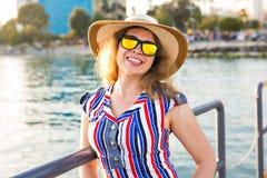 De zomervakantie, vakantie, reis en mensenconcept - glimlachende jonge vrouw die zonnebril en hoed op strand over overzees dragen Royalty-vrije Stock Afbeeldingen