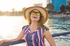 De zomervakantie, vakantie, reis en mensenconcept - glimlachende jonge vrouw die zonnebril en hoed op strand over overzees dragen Royalty-vrije Stock Foto's
