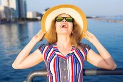De zomervakantie, vakantie, reis en mensenconcept - glimlachende jonge vrouw die zonnebril en hoed op strand over overzees dragen Stock Fotografie