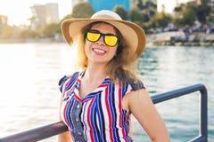 De zomervakantie, vakantie, reis en mensenconcept - glimlachende jonge vrouw die zonnebril en hoed op strand over overzees dragen Stock Afbeelding