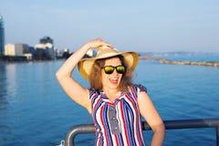 De zomervakantie, vakantie, reis en mensenconcept - glimlachende lachende jonge vrouw die zonnebril en hoed op strand dragen Royalty-vrije Stock Afbeeldingen