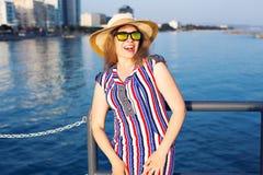 De zomervakantie, vakantie, reis en mensenconcept - glimlachende lachende jonge vrouw die zonnebril en hoed op strand dragen Royalty-vrije Stock Fotografie