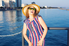 De zomervakantie, vakantie, reis en mensenconcept - glimlachende lachende jonge vrouw die zonnebril en hoed op strand dragen Stock Foto's