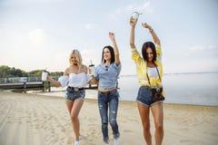 De zomervakantie, vakantie, reis en mensenconcept - groep glimlachende jonge vrouwen die op strand dansen royalty-vrije stock foto's