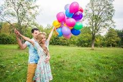 De zomervakantie, viering en het dateren van concept - koppel aan kleurrijke ballons in aard stock fotografie