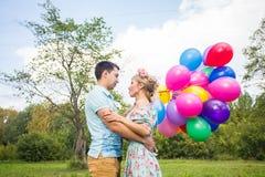 De zomervakantie, viering en het dateren van concept - koppel aan kleurrijke ballons in aard royalty-vrije stock foto's