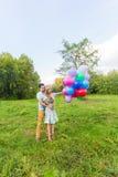 De zomervakantie, viering en het dateren van concept - koppel aan kleurrijke ballons in aard stock foto's
