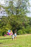 De zomervakantie, viering en het dateren van concept - koppel aan kleurrijke ballons in aard royalty-vrije stock foto