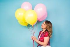 De zomervakantie, viering, vrouwen en mensenconcept - gelukkige vrouw met kleurrijke ballons binnen, achtergrond met stock foto