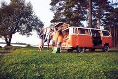 De zomervakantie, wegreis, vakantie, reis en mensenconcept - glimlachende jonge hippievrienden die pret over minivan hebben stock afbeeldingen